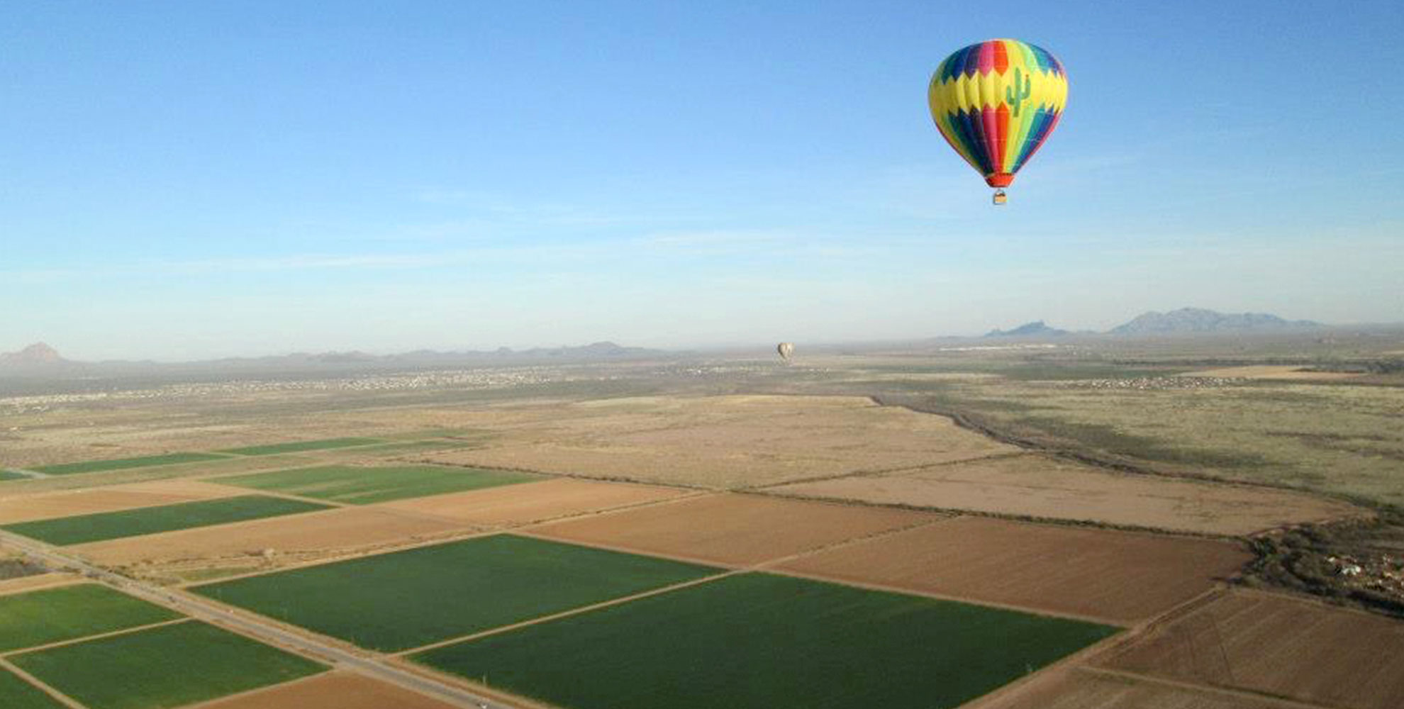 Two Hot Air Balloons Flying Over a Beautiful Landscape